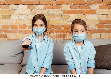 Selective Focus Of Siblings In Medical Masks Watching Movie At Home