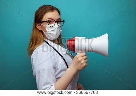 Female Doctor In Protection Suit And Glasses With Mask Holds Megaphone