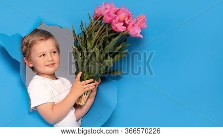 Young Little Caucasian Kid Holding Pink Bouquet Of Flowers Over Blue Background. Happy Boy With Smil