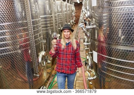 Young woman as a winemaker trainee with a glass of red wine in the winery
