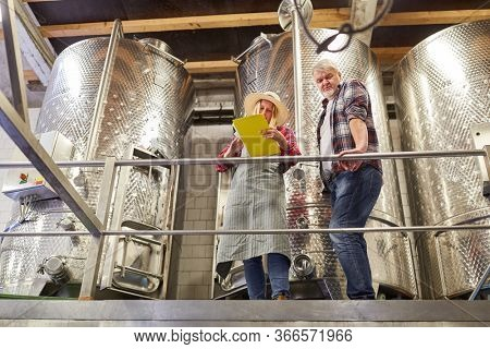 Winemaker team with checklist controls the wine production at the fermentation tank