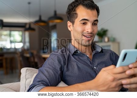 Happy smiling latin man with smartphone being surprised as reading message while sitting on sofa. Hispanic guy with cellphone relaxing at home while receive great news from friend.
