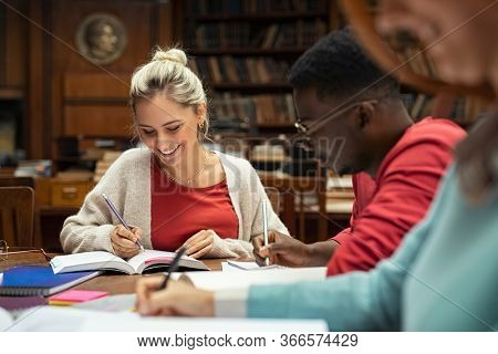 Group of smiling multiethnic students studying together at college library. Happy young woman making notes in library sitting with classmates. Girl in casual completing homework in high school.