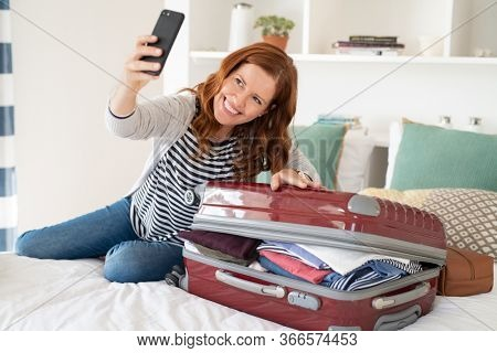 Beautiful mature woman taking selfie with overstuffed suitcase before leaving for a trip. Cheerful middle aged woman sitting on bed using smartphone taking picture with unpacked bag before vacation.