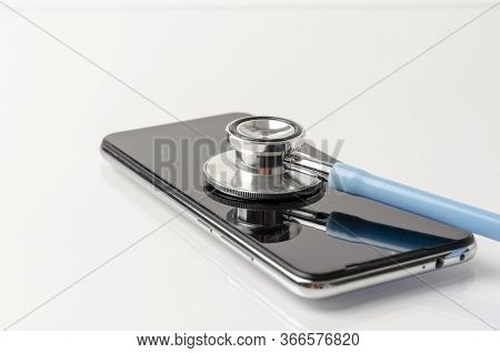Telemedicine Or Telehealth, Remote Doctor Video Chat Consultation Concept With Smartphone And Stetho