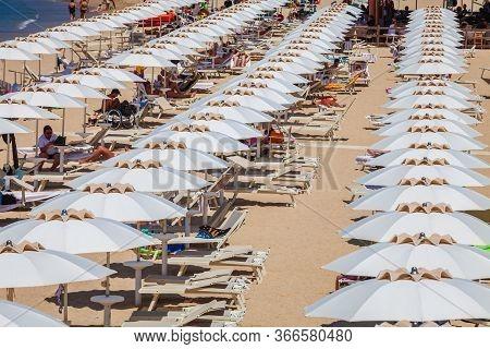 Procchio, Italy. June 28, 2016: Countless White Umbrellas. Social Distancing Summer Season. Many Peo