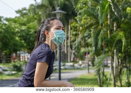 The Ypung Woman In Medical Protective Mask Relaxing In The Park.  Campaign To Use Protective Mask Fr