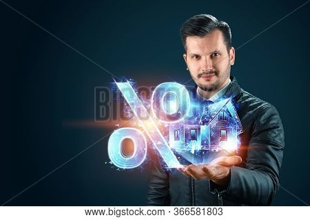 Mortgage Concept For Housing Mortgage Interest Rates. A Man Holds A Hologram Of A House And A Percen