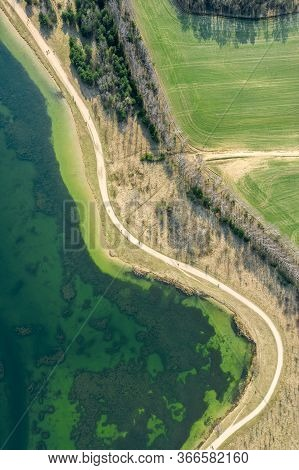 Aerial View Of Bicycle Lane Between Green Fields And Lake. Public Park In The Spring