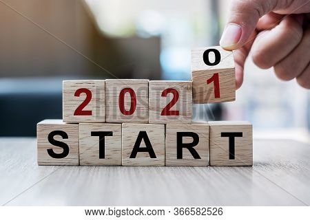 Businessman Hand Holding Wooden Cube With Flip Over Block 2020 To 2021 Start Word On Table Backgroun