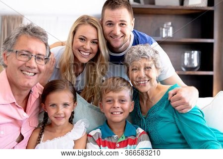 Portrait of a three generation Caucasian family spending time together at home, sitting on a couch, smiling and looking straight into a camera.
