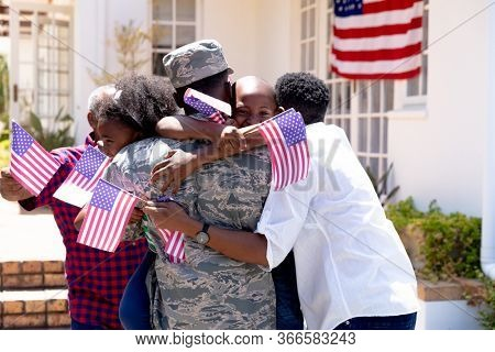 African American three generation family standing by their house, welcoming an African American solider wearing uniform, embracing and interacting.