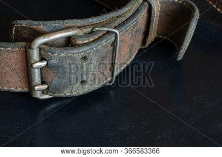 Cracked Very Old Leather Belt With A Double Metal Buckle. Close-up Of A Wide Dirty Belt Or Collar On