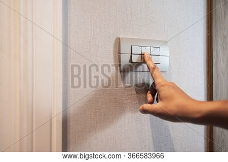 Closeup Of Asian Woman Finger Is Turning Off On Grey Light Switch Over Textile Texture Wall In The H