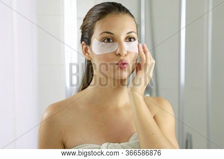 Attractive Woman Applying Anti-fatigue Under-eye Mask Looking And Kissing Herself In The Mirror In T
