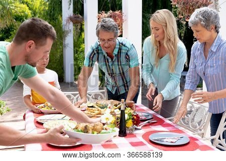 Caucasian three generation family preparing a lunch in the garden on a sunny day, setting a table and interacting.