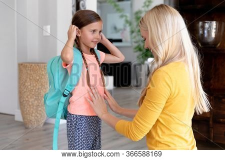 Caucasian woman with long blond hair helping her daughter wearing a green rucksack preparing for leaving to school.
