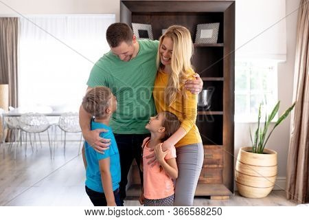 Caucasian family spending time together at home, standing in their sitting room, embracing, smiling and interacting. Social distancing and self isolation in quarantine lockdown.