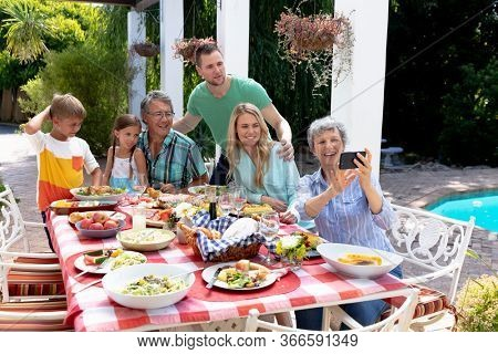 Caucasian three generation family spending time together in the garden on a sunny day, sitting by a table and having a lunch, while a senior woman is taking a selfie with her smartphone.