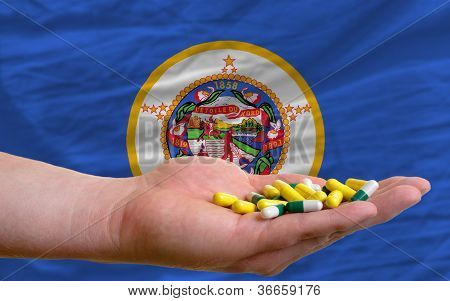 Holding Pills In Hand In Front Of Minnesota Us State Flag