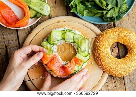 Bagel With Salmon. White Bagel With Fish And Herbs. Girl Is Preparing A Sandwich For Breakfast. Sand
