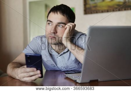 Sad Cute Young Man Holding A Smartphone In His Hand A Man Working On A Laptop Remotely. Fatigue From