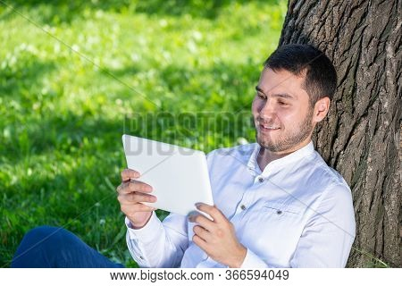 Man Using Tablet Computer Under Tree In Park On Sunny Day. Handsome Guy Looking At Tablet Screen. Ha