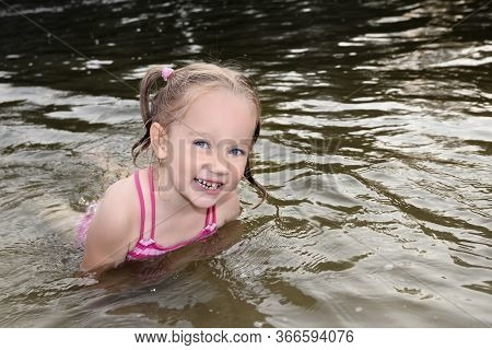 Little Girl Smiling In The River Water. Happy Fair-haired Child Playing In The Water On The River Be