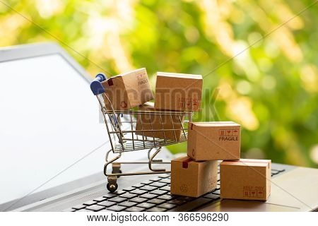 Online Shopping, E-commerce And Customer Experience Concept: Boxes In A Shopping Cart On A Laptop Ke