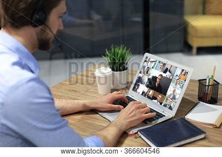 Businessman In Headphones Speak Talk On Video Call With Colleagues On Online Briefing During Self Is