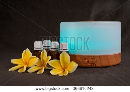 Oil Diffuser With Frangipani Flowers And Small Glass Essential Oil Bottles