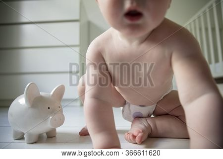 Cost Of Having A Baby And Childcare Concept. Young Child With A Piggy Bank