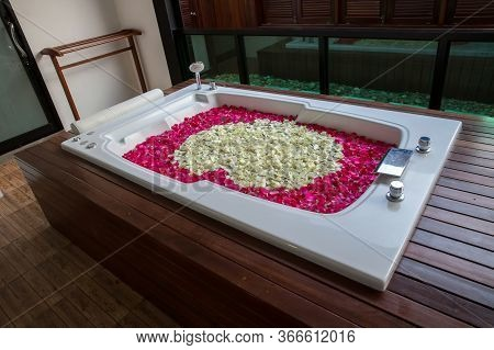 A Relaxing Bath With Rose. Bath Tub With Floating Petals. Rose Petals Put In Bathtub For Romantic Ba