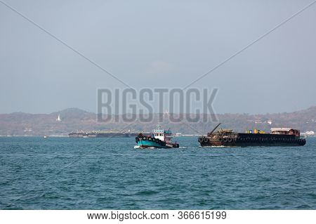 Small Towing Tugboat Dragging The Huge Dredger Ship In The Sea. Drilling Industry In The Ocean. Imag