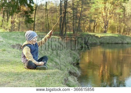 A Boy On The Riverbank In The Forest Plays With An Improvised Fishing Rod, Concept Happy Family Camp