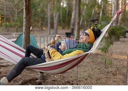 Mother Hugs Her Son Sitting In A Hammock In The Forest, Laughing And Rejoicing, Concept Happy Family