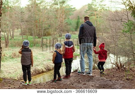 Young Man And Children Look At The River From A Cliff In The Forest, Dad And Four Children, Paternit