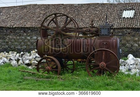 Rubble Surrounding A Rusted Steam Tractor Sitting Idle.