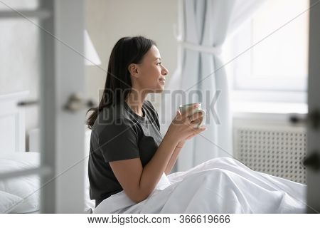 African Woman Wakeup Sitting In Bed Drinking Morning Coffee
