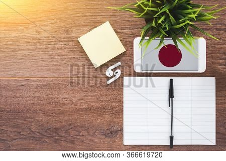 Japanese Flag On Smartphone On A Wooden Table, Notebook And Pen, Study Concept