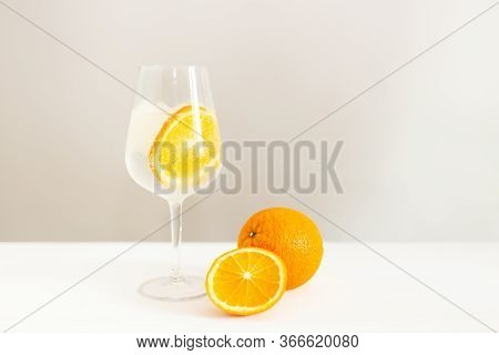 A Glass Of Cold Still Water With Orange Slice And Ice On Light Background. Healthy Lifestyle And A G