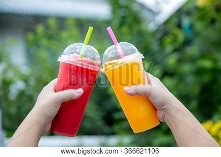 Fruit Smoothie. Hand Holding Plastic Cup Of Colourful Fruit Smoothie At Cute Cafe. Hand Holding Plas