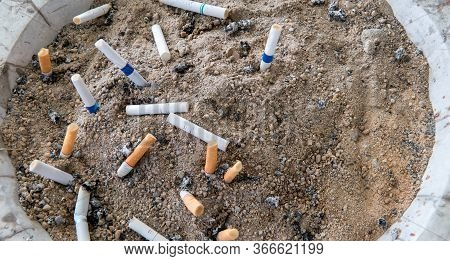 Many Cigarette Stub In Sand Ashtray. The Rest Of Cigarettes In The Ashtray. There Are Many Types Of