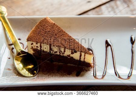 Tiramisu On White Plate . Delicious Tiramisu Cake With Coffee Beans And Fresh Mint On A Plate On A L