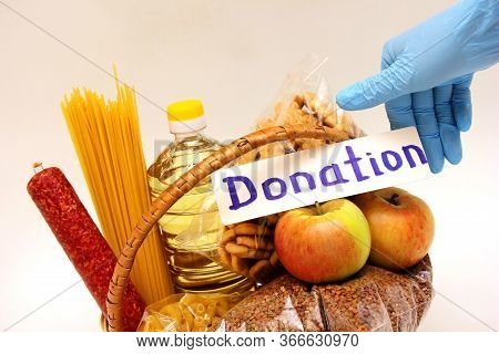 A Hand In A Rubber Glove Holds The Inscription Donation In The Basket With A Food . Social Assistanc