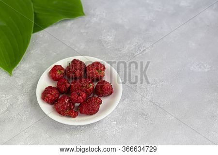 Ugly Natural Product Of Strawberries On A White Dish, Red Ripe And Strange Shapes On A Gray Backgrou