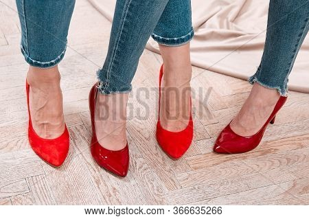 Four Girls Legs In Jeans And Red Shoes.