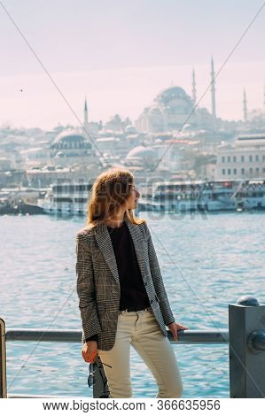 Beautiful Girl With Blond Hair Stands On Embankment Of Istanbul With View To Suleymaniye Camii And B