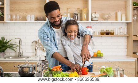 Cute Black Little Girl Enjoying Cooking Tasty Dinner With Lovely Daddy, Kitchen Interior, Panorama W