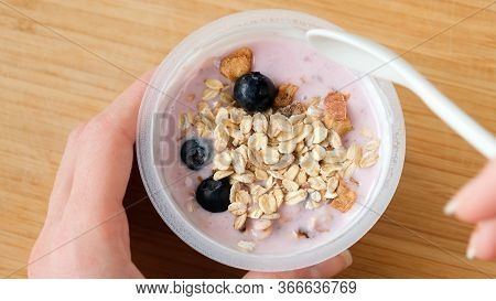 Blueberry Yogurt With Oat Muesli. Female Hands Holding Plastic Jar Of Yogurt With Muesli Or Granola.